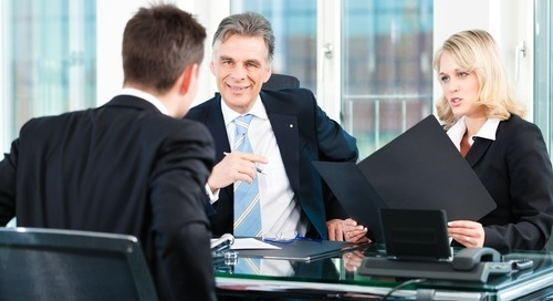 executive recruiting firms Milwaukee men sitting around a conference tables